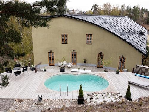 Baksidan av souterränghuset med flera våningar. Här finns uppvärmd pool, trädäck, stenbelagda terrasseringar och naturtomt.