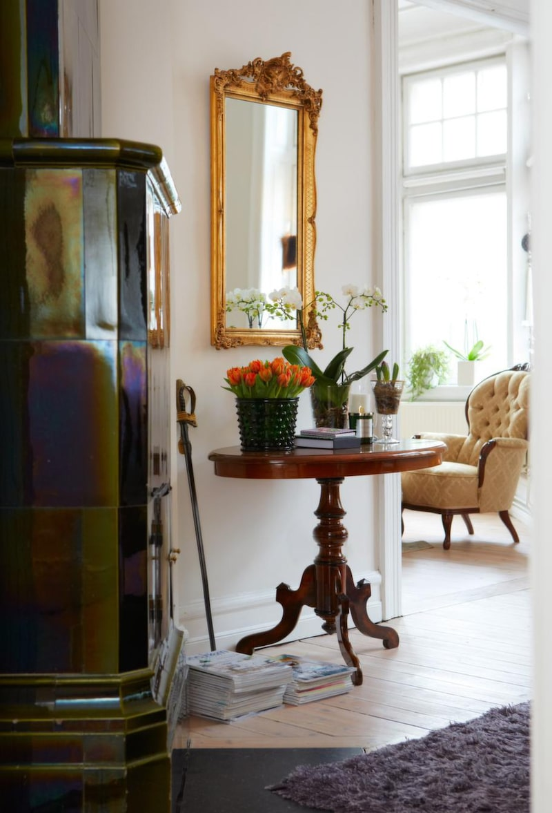 Personligt pyntat med orkidéer och tulpaner vid den mossgröna kakelugnen. Antikt sidobord i mahogny. Grön kruka Hortus i glas, Svenskt tenn.