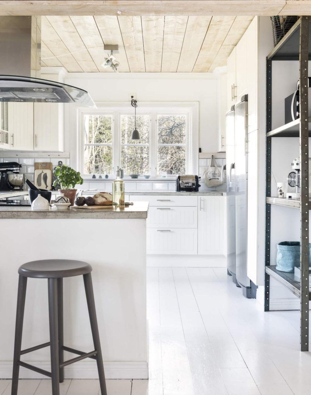 Köket är ljust med vita väggar och golv. Det vackra trätaket reflekterar ljuset från fönstren och förenar naturen med insidan av huset.