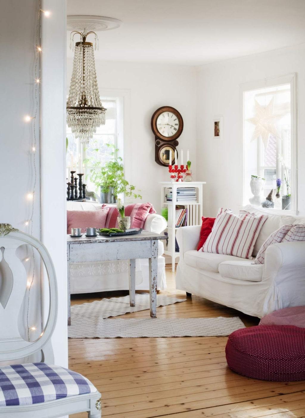 Det juligt röda är vackert mot det vita. Sofforna kommer från Ikea, kuddar, mattor och sittpuff från Utängs antik. Klockan är från Lindas farföräldrars hem. Den enkla ljusslingan vid dörrposten skapar stämning oavsett årstid.