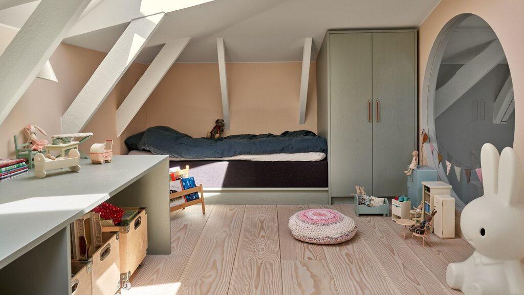 Ett av två rymliga sovrum på övre plan. Charmigt med snedtak, takfönster, bjälkar och runt fönster med utsikt till nedre plan. Platsbyggda skåp, bord och annan förvaring.