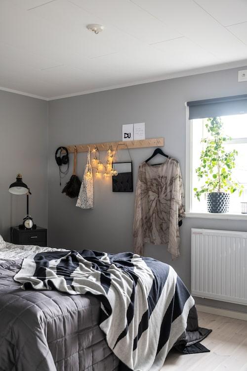 Sovrummet är målat i en lugn grå nyans. En knopplist fungerar både som hängare och dekoration.