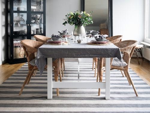 Camilla har dukat för fyra i vardagsrummets bortre del. Bord, stolar och lampa är från Ikea och skåpet kommer från Ellos. Mattan är från Tine K home.