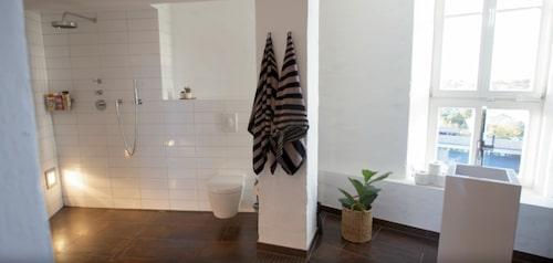 I det helkaklade badrummet kan du se på den fantastiska utsikten när du står och tvättar händerna vid det dopfuntliknande handfatet.