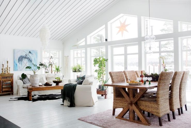 Det stora vardagsrummet på den övre våningen har utsikt över sjön genom stora, heltäckande fönster. Soffgruppen kommer från Ikea, och bordet är köpt på Asko.