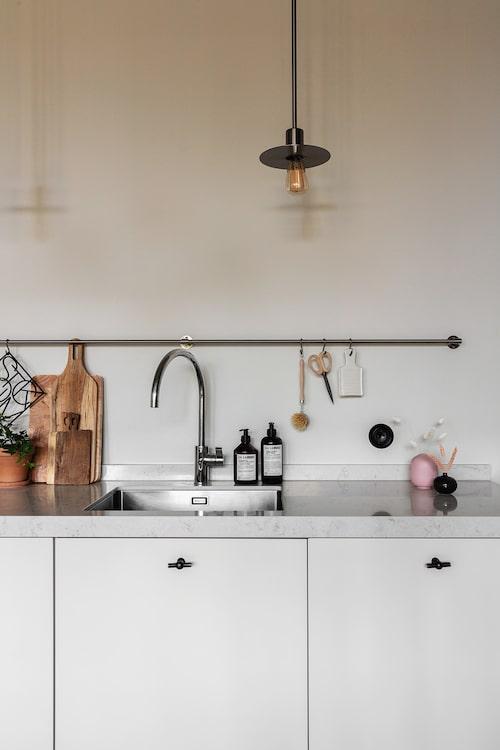 Köksluckornas ljusgrå nyans skapar en fin kontrast mot de svarta beslagen och bänkskivan i sten. Köksluckor, Lidhults. Blandare, Dornbracht. Beslag, Giara Design. Skärbrädor, köpta i Australien. Lampa, Rubn, design Niclas Hoflin.