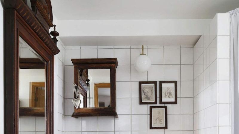 <p>Vitt och trä. Lantlig stil i badrummet med rutigt draperi och mörkt trä. Träskåpet på väggen är från Indiska.</p>