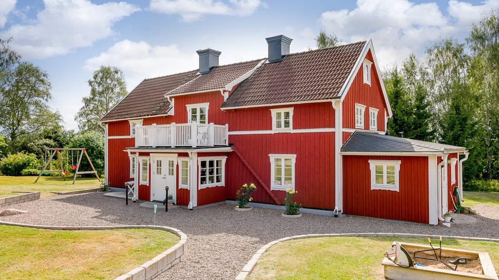 Rött hus med vita knutar och åkrar runt omkring, mer svenskt än så här kan det knappast bli.