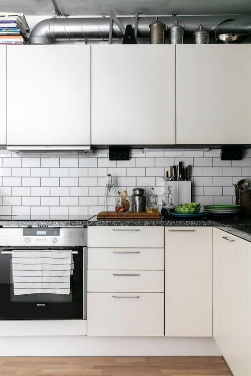 Köket ligger i vinkel från matrummet. Synliga ventilationsrör ger karaktär till lägenheten. Porslin från Mateus. Karafferna är fyndade på auktion. Citronpress från Alessi. Burkarna och bokstaven ovanpå skåpen kommer från Anettes tidigare butik Boudoir i Ystad.