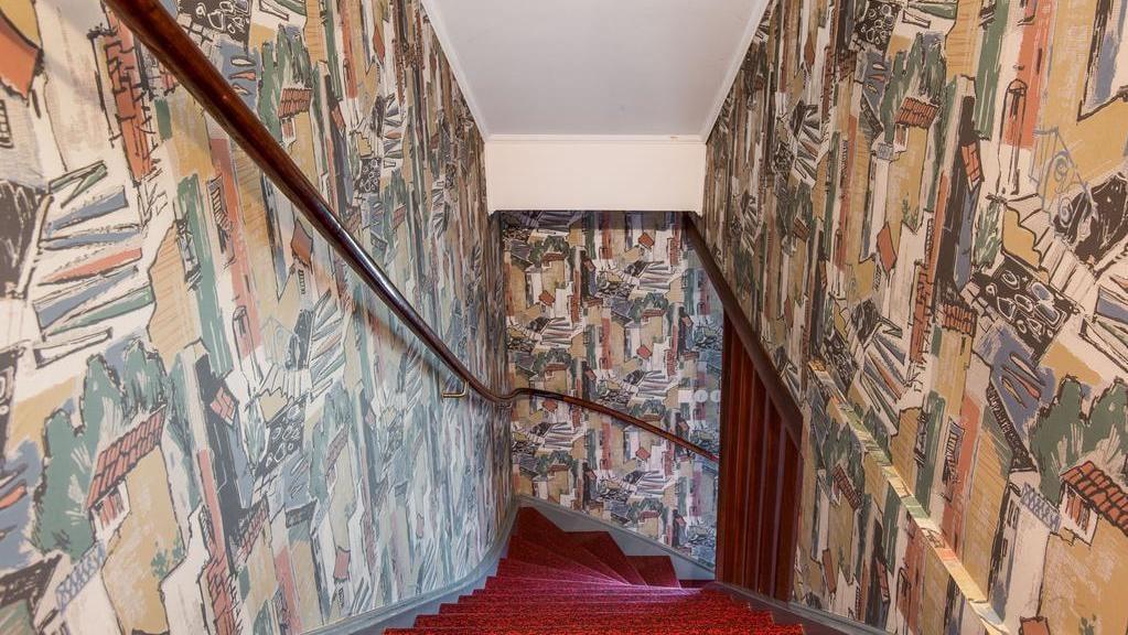 Trappan som leder upp till den inredda vindsvåningen är klädd med knallröd heltäckningsmatta. De mönstrade tapeterna innehåller alla dess färger.