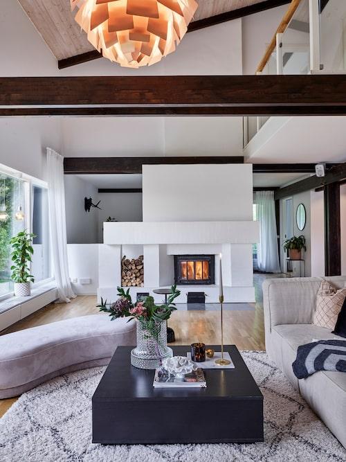 """Den vitputsade eldstaden är som ett smycke för vardagsrummet och ger härlig värme. """"Vi tycker mycket om vårt vardagsrum, det känns aldrig trångt när vi har vänner på besök"""", säger Linnea. Ljusstakar, Skultuna. Soffbordet är köpt second hand."""