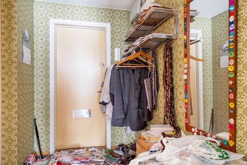 Mörk korthårig heltäckningsmatta och tapetserade väggar med mönster i hallen. Plats för avhängning av ytterkläder och förvaringsmöbel.