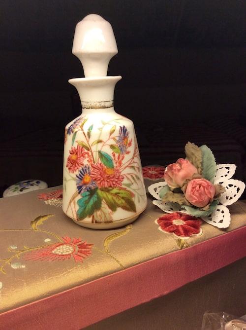 Förr i tiden var det vanligt att man köpte sig en tom, vacker flaska och fick den fylld med Eau de Cologne eller parfym. Denna vita glasflaska med målade blommor är antagligen av tyskt fabrikat, 1880-tal.