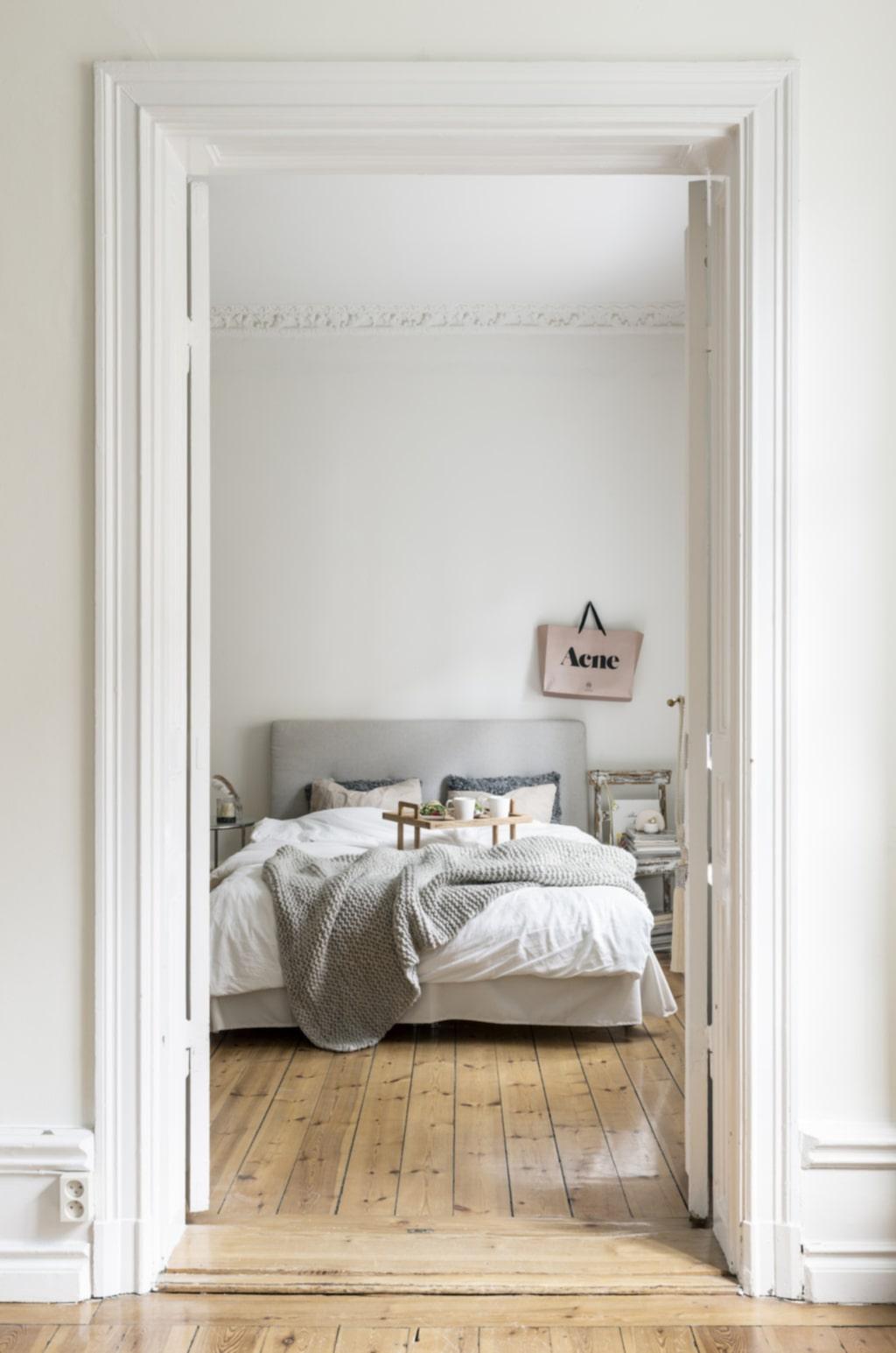 Ljusa toner. Sovrum och vardagsrum ligger i fil med pardörrar som binder ihop rummen. Grovstickad ullpläd från By Pias. Sängbricka och porslin från Gant, Vålamagasinet. Fårskinnskuddar från Shepherd.