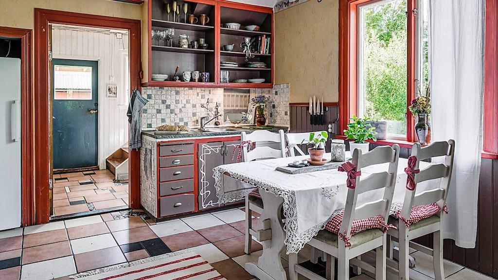 Köket med stenplattor på golv och röda lister. Hall i bakgrunden.