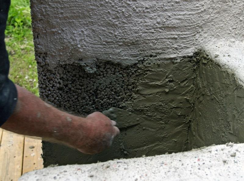 2. Slamma ytan. Blanda murbruket så att det blir något lösare än när du murade lecablocken. Använd en murslev och kasta (snärta) upp bruket mot stenarna, om det inte fastnar kan det behövs mer vatten i blandningen. Släta ut bruket med sleven lite grovt.