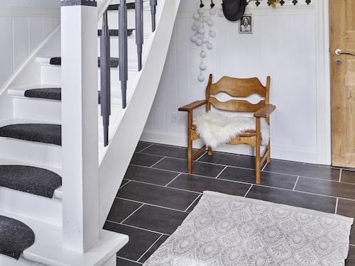 Hallen ligger placerad mitt i huset och är generös och luftig. Stolen är fyndad på loppis och designad av Henning Kjärnulf. Mattan kommer från Netto.