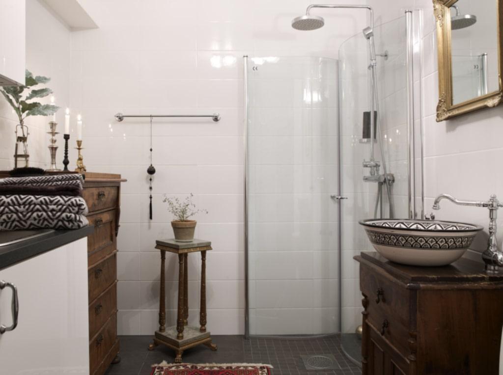 Personligt. Badrummet med vitt kakel och svart klinker har fått personlig inredning då de är inrett med gamla, antika möbler som mixas med traditionella vita skåp.