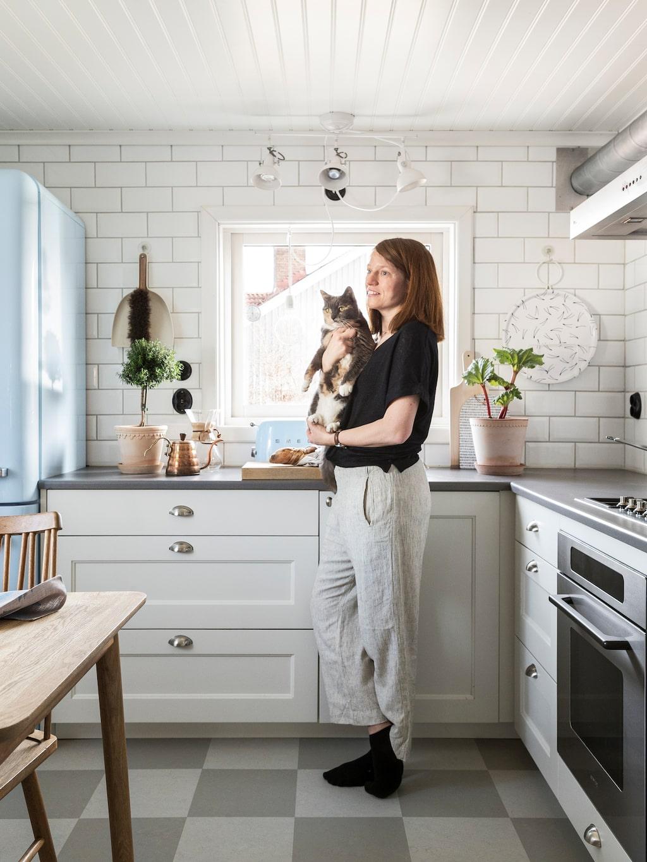 Köket har fått en lekfull lantlig stil med schackrutiga linoleummatta och 1950-talsinspirerad tapet. Köksskåpen är platsbyggda, tillverkade av ett snickeriet Strömdal i Borås. Bord och stolar, Hans K.