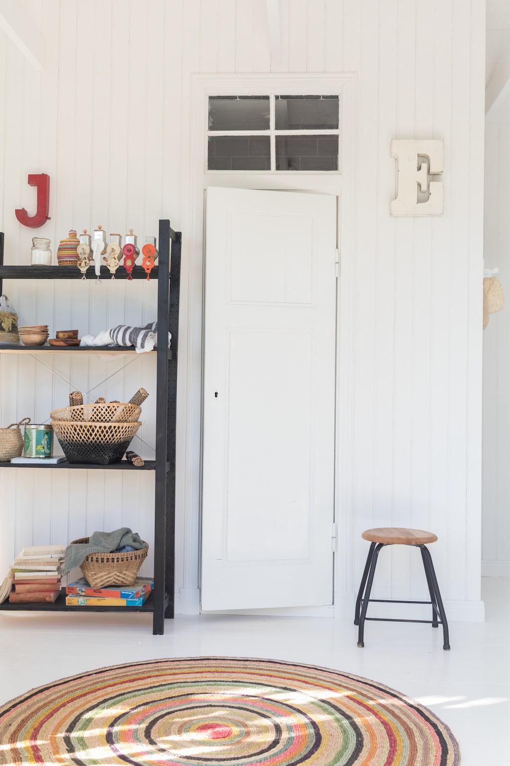 En klassisk lagerhylla fungerar som avställningsyta. Hyllan Ivar från Ikea var från början trävit, men Nicole har målat den svart.