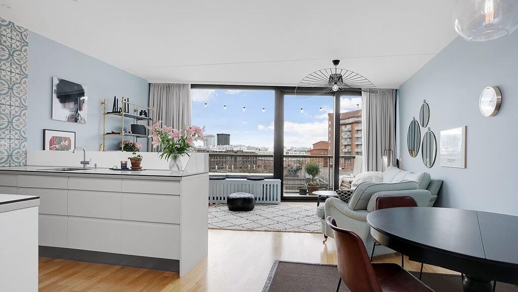 Det är öppen planlösning mellan kök och vardagsrum på etagéplan, och direkt utgång till en av våningens två terrasser. Stilsäkert marockanskt kakel bryter av mot vita luckor, och den vita snygga bänkskivan med generös arbetsyta.