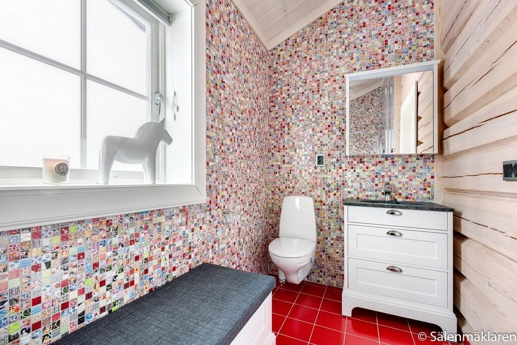 Ett av badrummen, med färggrann moasik på väggen.