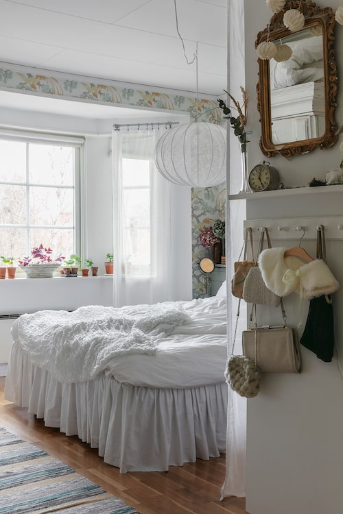 I sovrummet hänger en vacker guldspegeln som tidigare tillhört Mias farmor. I spegeln skymtar ett stort och tungt linneskåp som Mias föräldrar hittade i ett soprum när hon var liten, många lager färg gömmer sig under det nu vitmålade skåpet. I taket ovanför sängen hänger en rund lampstomme som Mia klätt in med spetstyg från Ikea. På fönsterbrädet står pelargonsticklingar på rad.