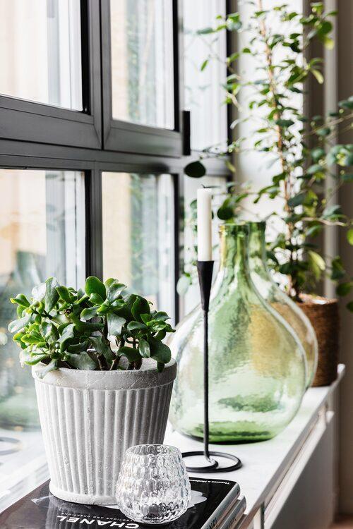 De långa fönsterbrädorna som löper längs alla fönster har plats för mycket växter och prydnadssaker. Kruka, Plantagen, Glasflaskor, H&M Home.