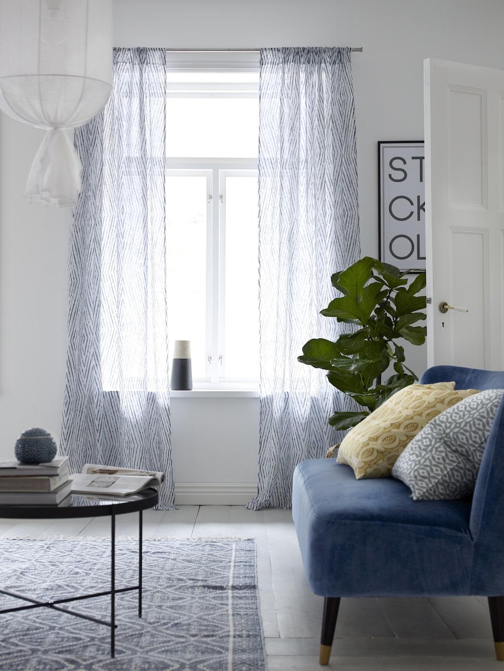 Det trendiga blåa i soffan matchas med grått, och linne runt lampan.