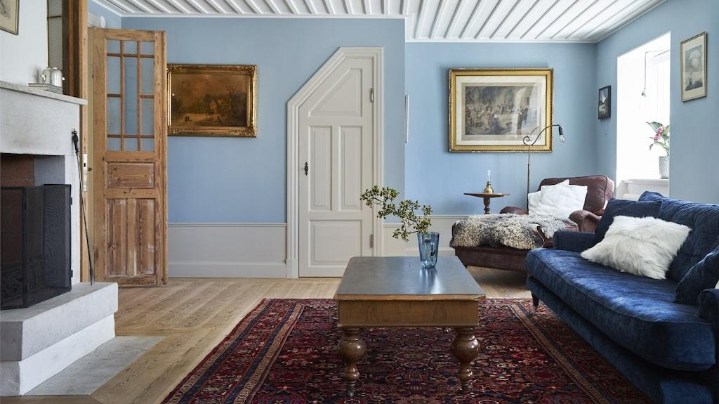 Öppen spis i vardagsrum med gammal stil som blandas med nytt.