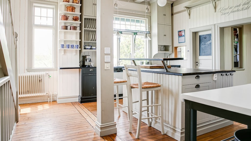 På andra våningen ligger köket med stor köksö med bardel och bänkskiva i trä och laminat.