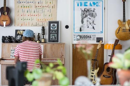 Mikael tar plats vid musikrummets piano. Priser och affischer vittnar om en spännande musikkarriär. Skolaffischen med noter är köpt på Kannibalmuseet i Önneköp.
