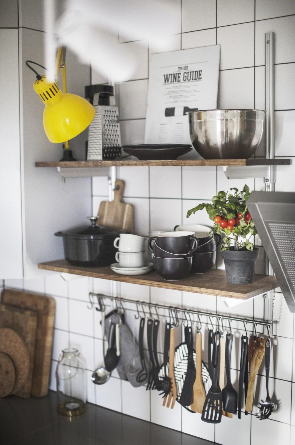 Öppna hyllor. Malin har samlat alla köksredskap på hängare som Johan har konstruerat. Hyllan är betsad i samma ton som golvet. Lampan kommer från Ikea och är spraymålad.