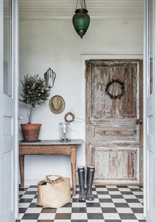 Den gröna taklampan fanns i huset när Susanne och Hans-Evert flyttade in. Sidobordet i trä är ett gammalt slaktbord. Ljuslykta i glasbehållare från loppis i Småland. Korgväska från en utlandsresa.