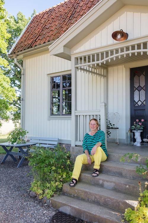 Det stiliga gamla trähuset har en inbjudande entré. Annette trivs i skuggan på trappan.