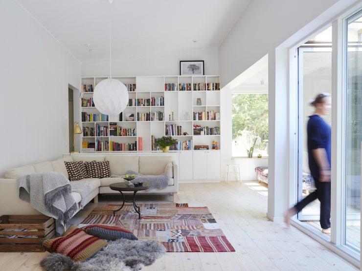 I det ljusa vardagsrummet står en soffa i klassisk design från Larsson furniture. Kuddar från Svenskt tenn, matta och soffbord från Casa Marrakech. Lampan är köpt på Gärsnäs. De breda, skjutbara fönsterpartierna vetter ut mot atriumgården som är familjens andra vardagsrum.