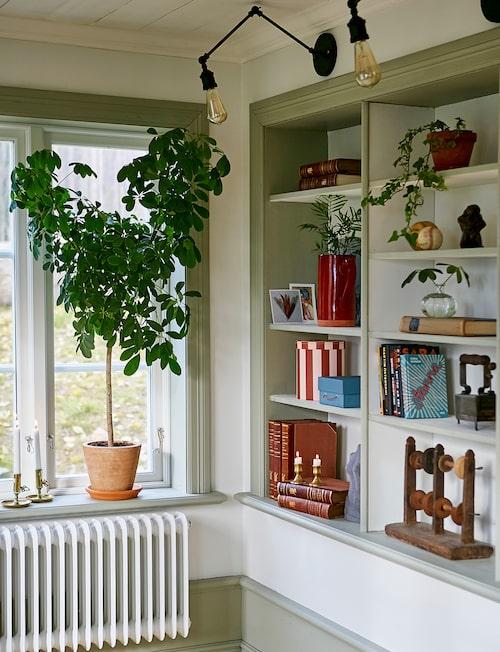 Den platsbyggda bokhyllan rymmer både böcker och favoritprylar och är det bästa med vardagsrummet enligt Clara. De svarta vägglamporna har Clara beställt från en amerikansk webshop.
