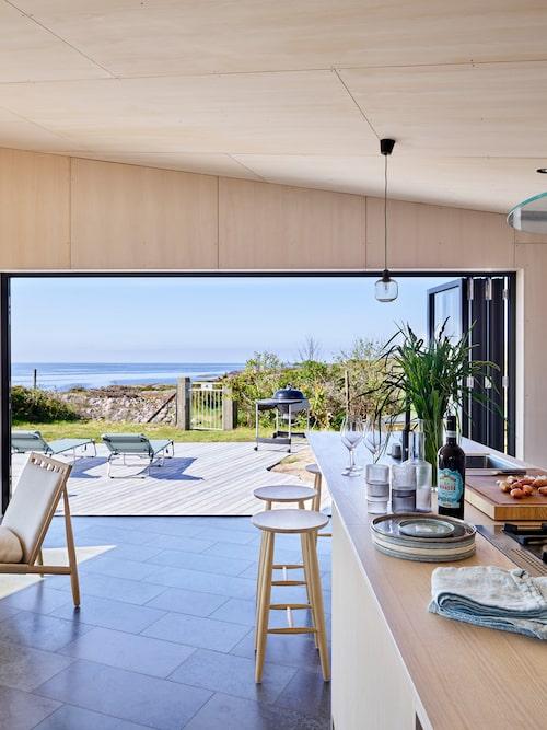 Hussidan i söderläge mot havet har fönsterdörrar som kan skjutas åt sidan så att gränsen mellan inne och ute suddas ut. Barstolar från Norrgavel. Kök i vitpigmenterad ask, Himlekök.