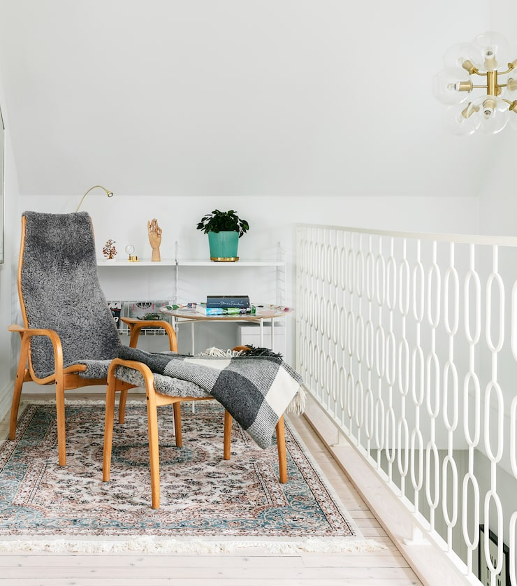En trappa upp finns en liten myshörna. Laminofåtölj, Swedese. Hylla, String. Trappräcket är specialbeställt för att passa husets stil. Takpendel Tage, Pholc