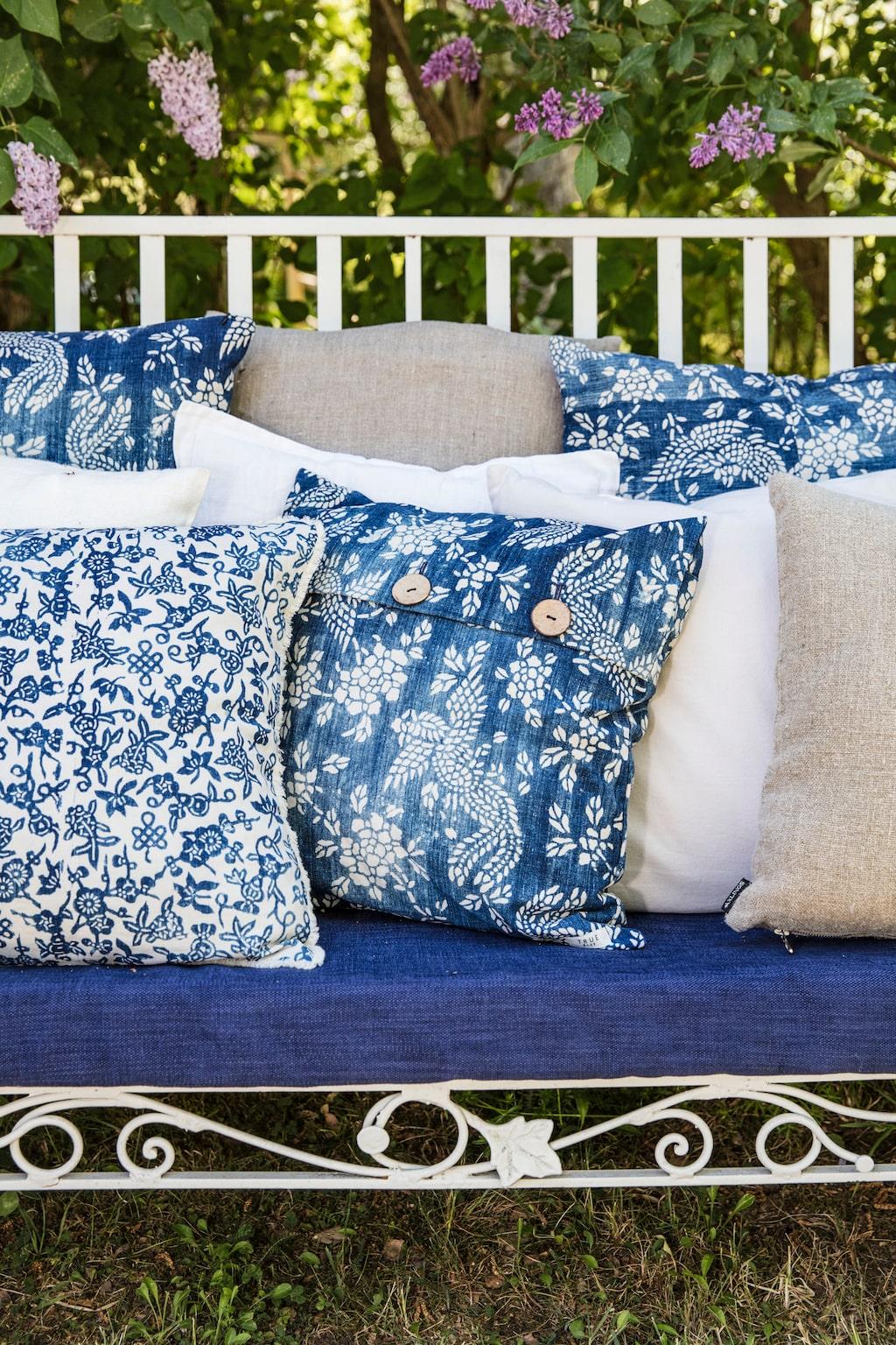 Stor blåvit vintagekudde med indigotryck, 950 kronor, vit kudde med blått mönster, 600 kronor, båda True Blue. Ljusblå kudde, 239 kronor, naturfärgad kudde, 219 kronor, båda Axlings linne.