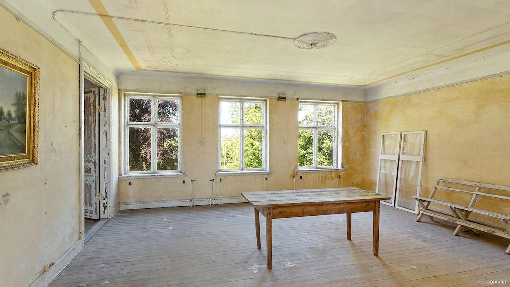 Salen. I taket ser man en gammal jugend-takmålning samt en takrosett som vittnar om husets storhet en gång i tiden.