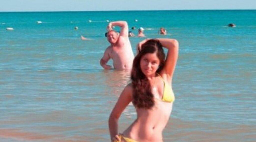 Den här tjejen poserar helt omedveten om den lustige skojaren bakom hennes rygg.