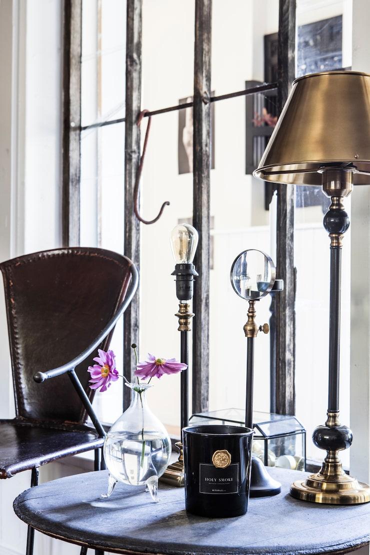 Bordslampor och glasbox från Mio. Förstoringsglas på fot från Posh living. Doftljus från Rituals. Stol i järn från Indori är ett älskat loppisfynd. Bordet som också är i järn är egentillverkat.