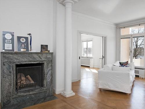 I sällskapsrummet finns en magnifik öppen spis i marmor, pelare och stora fönsterpartier.