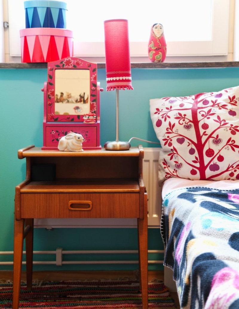 Lampskärmen inne i Emblas rum har Sara pyntat med fina band och små fransbollar. Nattduksbordet i teak är second hand.