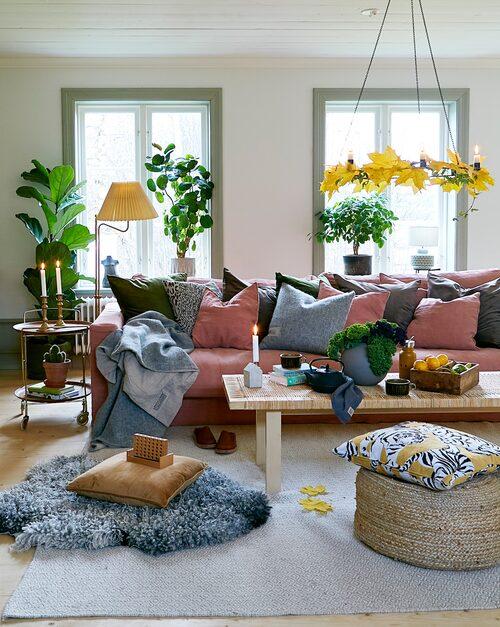 Familjens efterlängtade vardagsrum har nu en ny rymlig soffa. Soffa,  Sweef. Sammetskuddar, Boel & Jan. Ljuskrona, Ernst. Grå ull- och linpläd och kudde i samma färgställning, Lovely Linen. Gul- och svartmönstrad kudde, äldre från Åhléns. Tofflor, Docksta. Puff, Indiska. Soffbord, Ikea. Lampan är fyndad på en loppis i Piteå för många år sedan. Sidobordet på hjul har Clara fått av sina föräldrar.