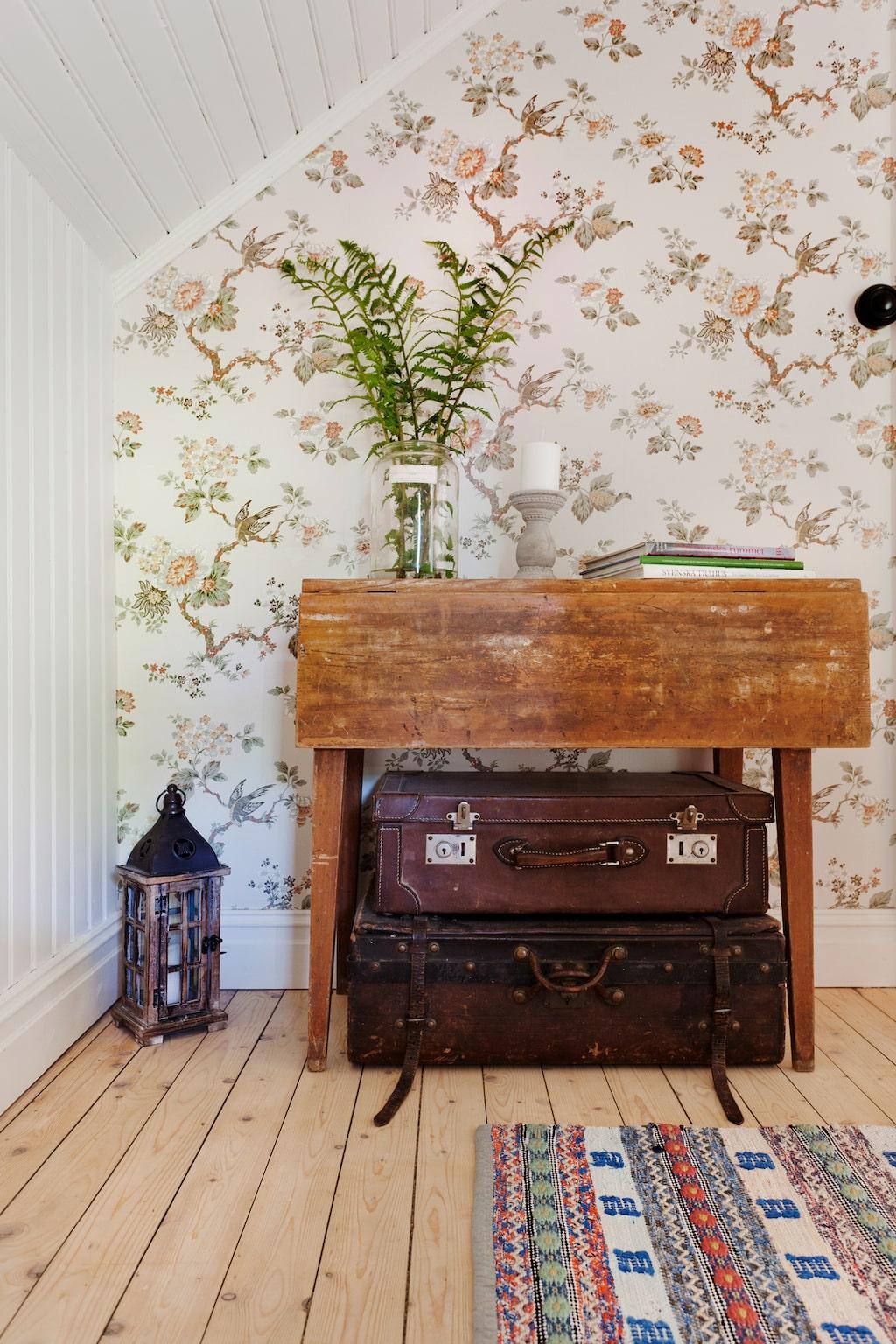 Loppisfyndade väskor och bord. Tapeten kommer från Boråstapeter ur kollektionen Falsterbo 2.