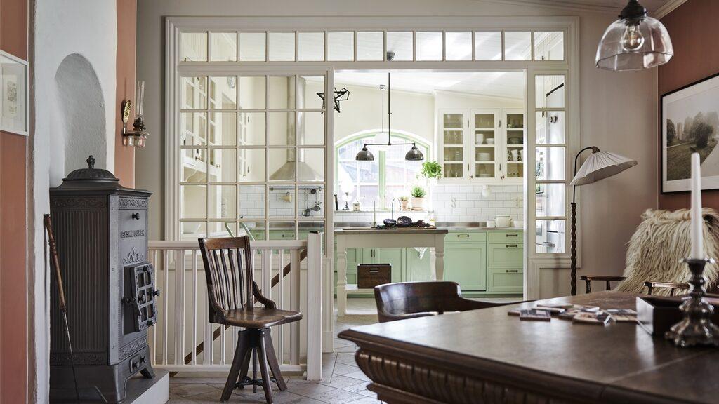 Utsikten från villans matsal, som har en vacker gjutjärnskamin, till det stora, ljusa köket där säljaren har byggt precis allting, in i minsta detalj, för hand.