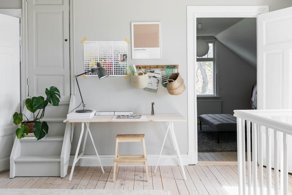 I övervåningens hall har Moa skapat en arbetsplats; hon studerar inredning på halvtid. Den lilla trappan och dörren leder till husets tornrum. Bordet är egentillverkat med ben från Ikea. Därifrån kommer också pallen och bordslampan.