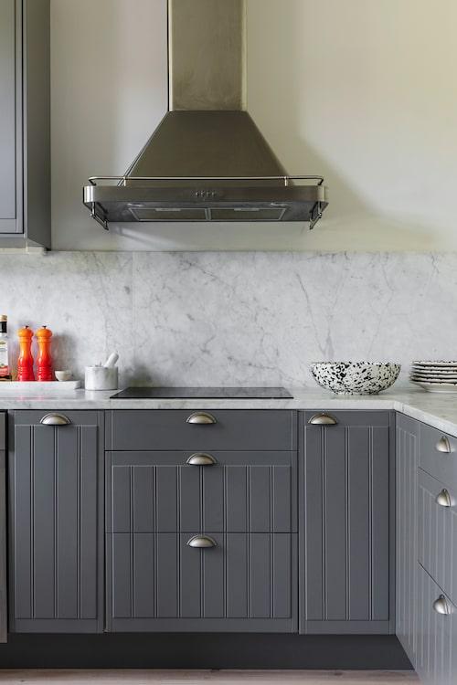 I renoveringen målades köket grått och fick nya bänksskivor och stänkskydd i marmor. Skål och fat från Zef Design, salt- och pepparkvarnar från Le Creuset. Morteln är köpt på Borett.